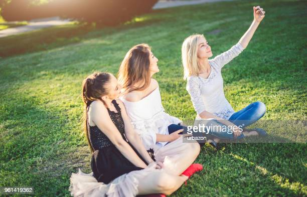 Three beautiful women sitting on grass in park and make selfie.