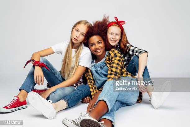 três meninas novas bonitas que sentam-se no estúdio - modelo profissional - fotografias e filmes do acervo