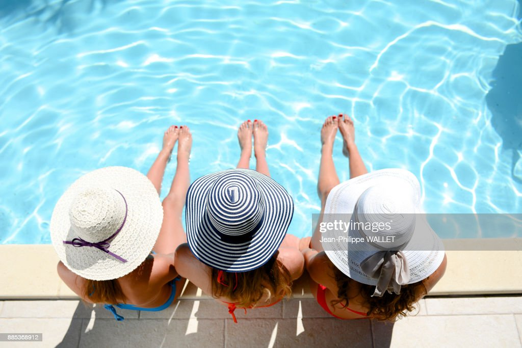Three beautiful young woman with swimsuit and sun hat sitting by the poolside of resort swimming pool during summer holiday. : Stock Photo