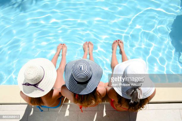 Three beautiful young woman with swimsuit and sun hat sitting by the poolside of resort swimming pool during summer holiday.