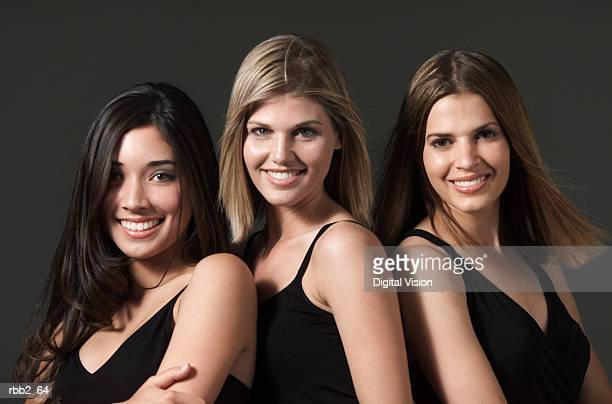 three beautiful young women dressed in black tank tops smile playfully into the camera - digital desire fotos stock-fotos und bilder