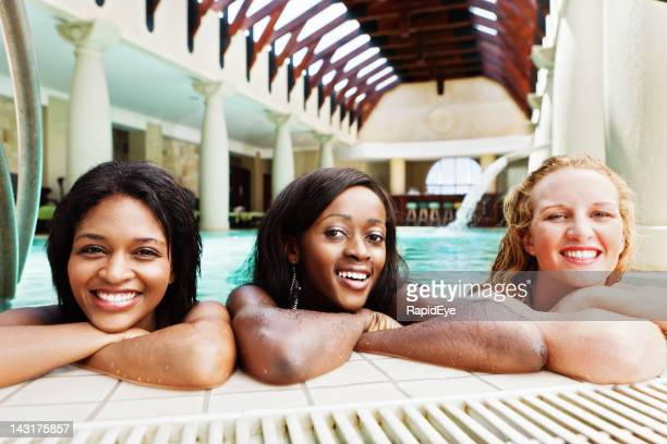 Three beautiful young women smile at edge of spa pool