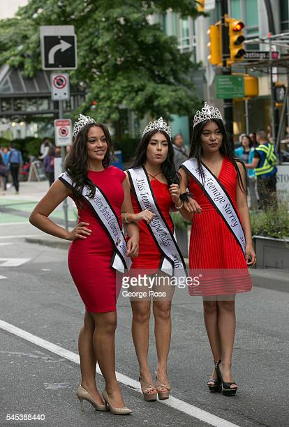 Three beauty pageant queens walk arminarm in the Canada Day Parade along Burrard Street on July 1 2016 in Vancouver British Columbia Canada Vancouver...