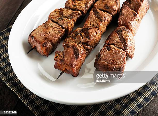 Three beef kebabs arranged on a white platter