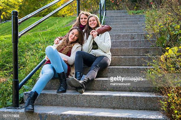 Three best friends on stairs outside, horizontal.