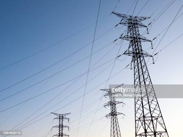 three big electrical towers of high tension for the distribution of electricity on a blue sky. - power station stock pictures, royalty-free photos & images