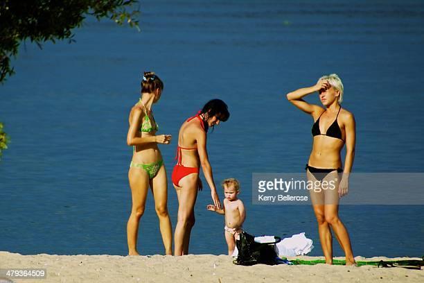 Three bikini clad women and a toddler stand on a beach. A woman in a black bikini shades her eyes from the sun. A woman in a green bikini looks away...