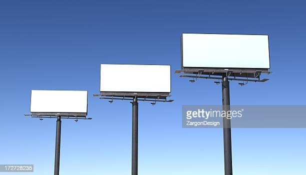 Three billboards isolated against blue sky