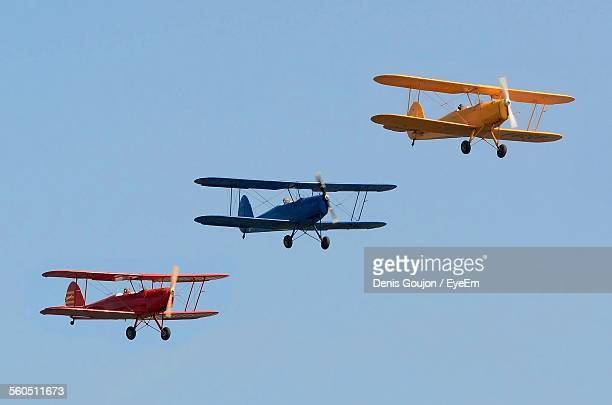 Three Biplanes Flying In Sky