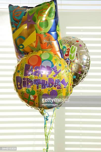 Three birthday balloons in office