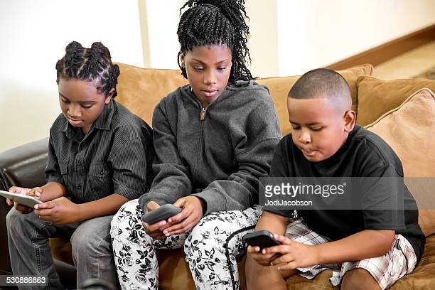 Three black children playing games on their electronic devices