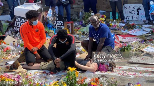 Three black men and a white man play the arrest of George Floyd at a makeshift memorial in Minneapolis Minnesota on June 1 2020 A white man lies on...