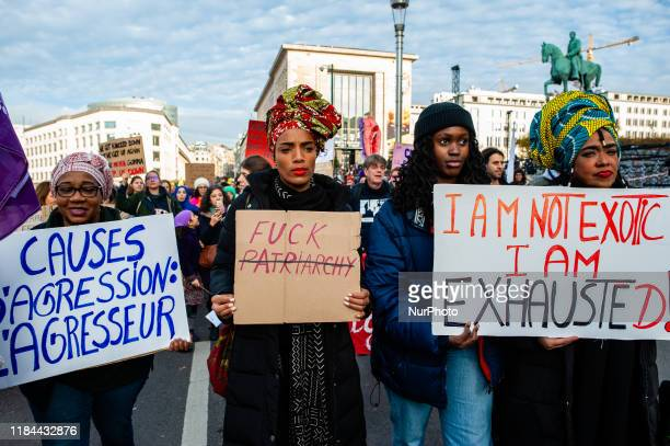 Three black women are holding placards, during the demonstration stop violence against women, in Brussels on November 24th, 2019.