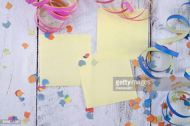 Three blank adhesive notes, confetti and streamers on wood