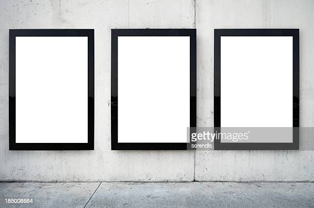 Three blank billboards on wall.