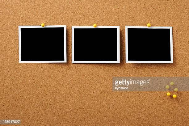 Three blank Polaroid pinned on cork board with yellow thumbtack