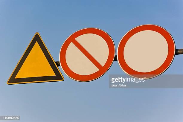Three blank street warning signs against blue sky.