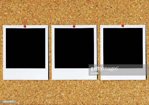 three blanked-out polaroid instant photographs on a cork notice board