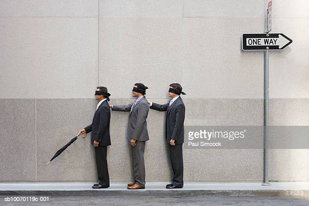 Three blindfolded businessmen on street