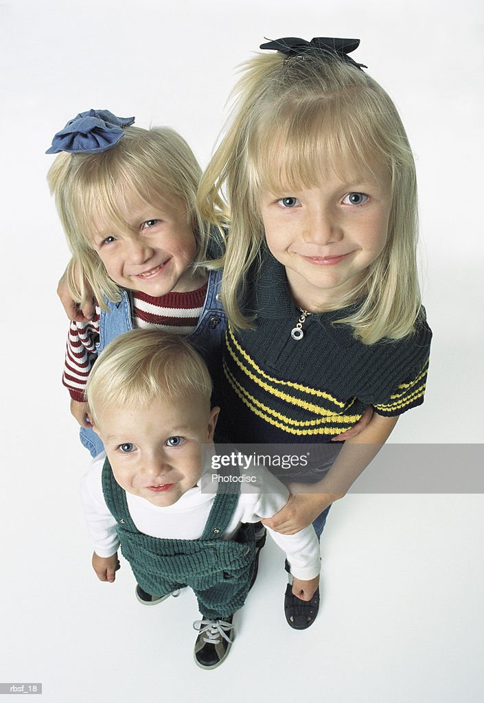 three blonde siblings stand together smiling with bows in hair : Foto de stock