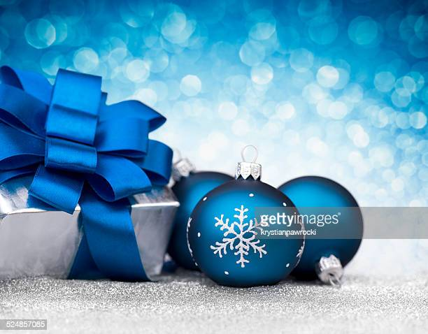Three blue bauble and silver christmas gift on glitter