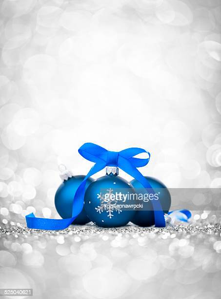 Three blue bauble with ribbon, christmas tree decoration and glitter
