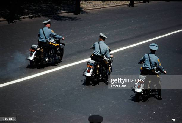 Three blue shirted New York policemen on motorbikes are leading a street parade