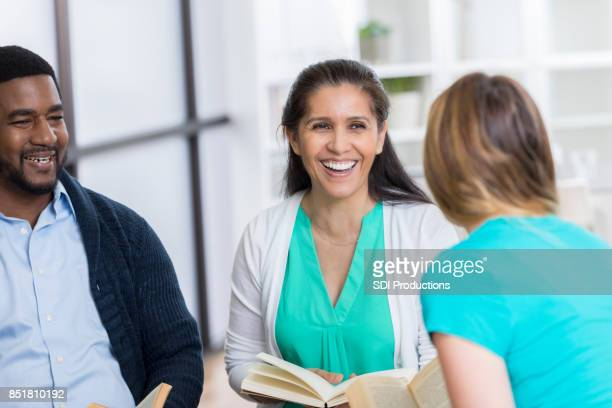 three book club members enjoy lively discussion - book club meeting stock pictures, royalty-free photos & images