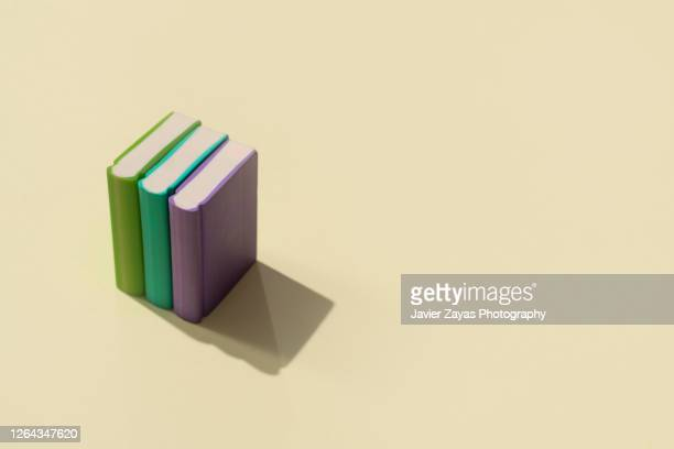 three books on a pastel colored background - dictionary stock pictures, royalty-free photos & images