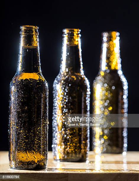Three  bottles of beer of with the crystal misted with water drops on a table of wood