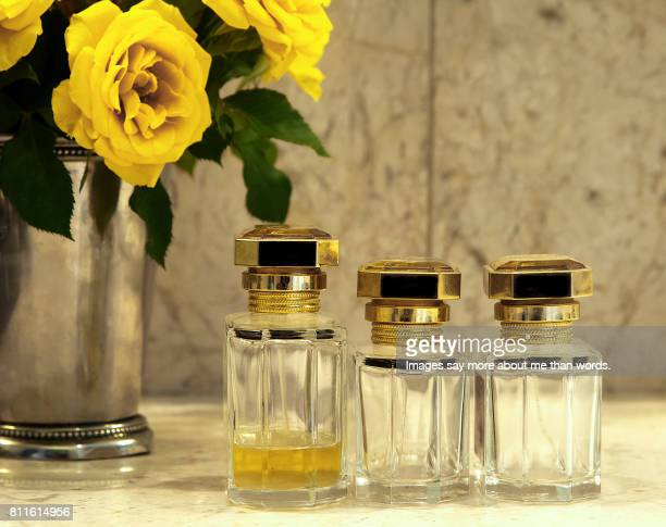 Three bottles of perfume: two empty and one almost finished. Silver vase with yellow roses. Still Life