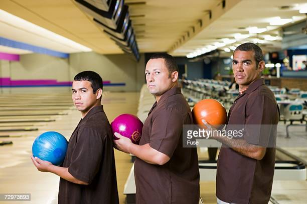 Three bowlers carrying bowling balls