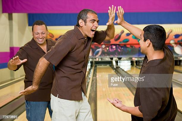 Three bowlers doing high-fives