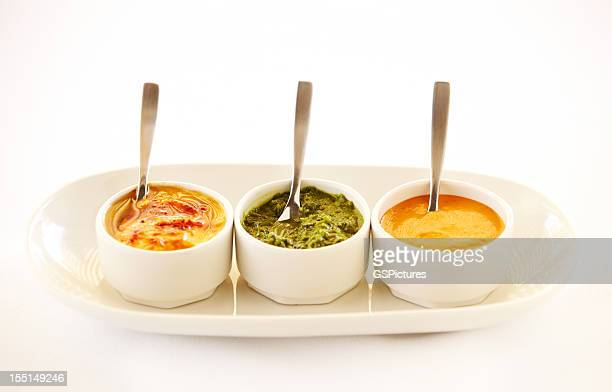 Three bowls of different dips in a row