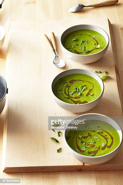 Three bowls of spinach soup on wooden surface