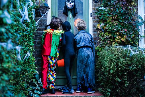 Three boy in halloween costumes, standing at door, trick or treating, rear view - gettyimageskorea