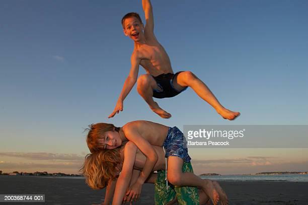 three boys (9-14 playing at beach, summer - jungen in badehose 12 jahre stock-fotos und bilder