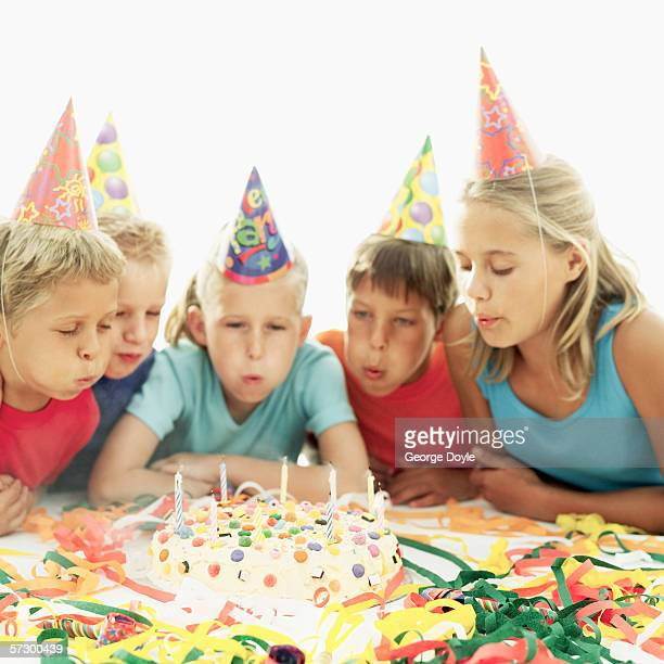 three boys and two girls (6-12) at a birthday party blowing out candles on a birthday cake - 12 13 jaar stockfoto's en -beelden