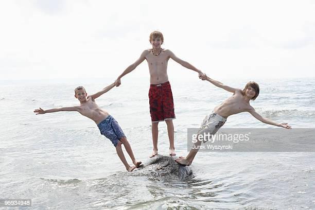 three boys balancing on a rock at the beach - jungen in badehose 12 jahre stock-fotos und bilder