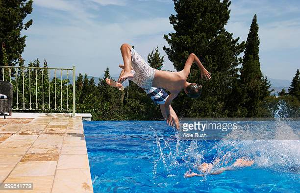 Three boys diving into apartment swimming pool