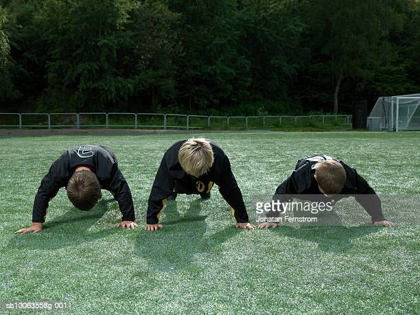 three boys (9-10 years) doing push ups on soccer field - 8 9 years stock pictures, royalty-free photos & images