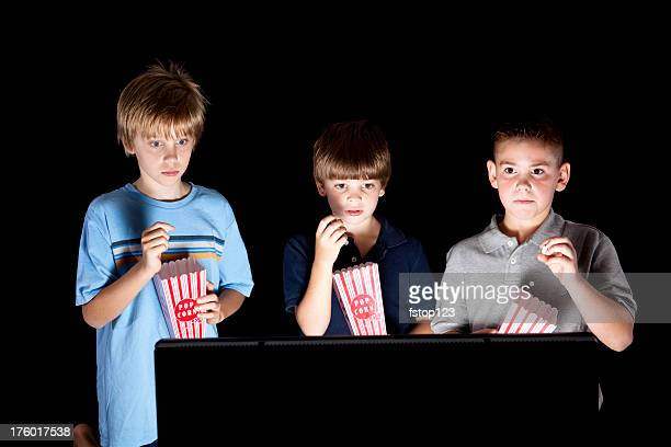 Three boys eat popcorn and watch television together.
