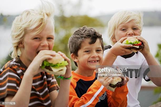 Three boys eating hamburgers outdoors Sweden.