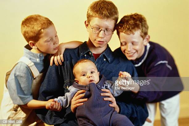 three boys (8-14) holding baby (3-6 months), close-up - 6 11 months stock pictures, royalty-free photos & images