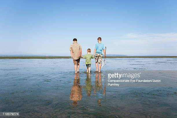 """three boys holding hands and walking in the water - """"compassionate eye"""" foto e immagini stock"""