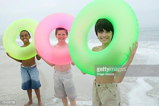 Three boys holding inflatable rings