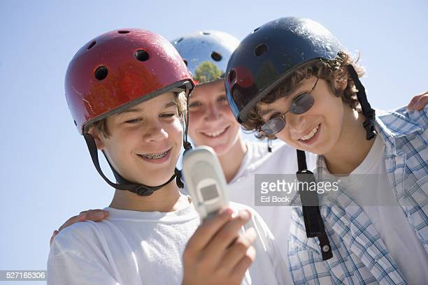 Three Boys in Helmets Checking Cell Phone