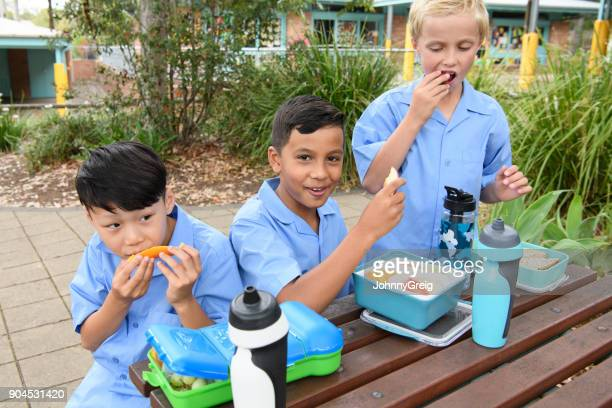 Three boys in school playground at lunch time eating packed lunch