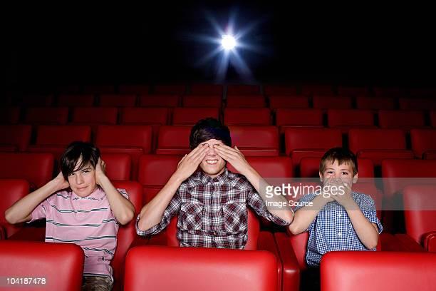 Trois garçons dans le cinéma devant les yeux, des oreilles