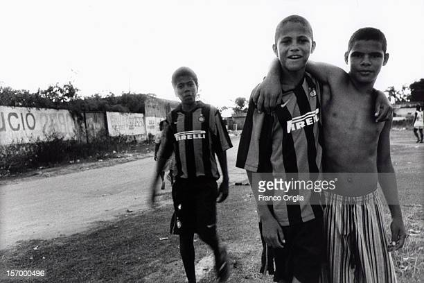 Three boys involved in the Intercampus project return after traking part in a football training session at the favelas of Santo Andre on December 13...